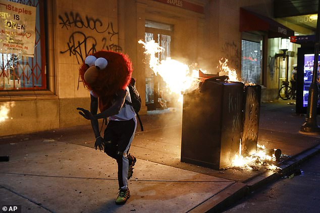 A man in an Elmo mask dances at a fire in Philadelphia on May 25, 2020 during protests