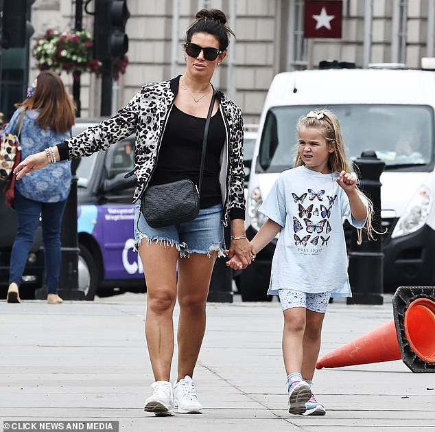 Stunning: The mom of five pulled her brunette up into a high bun and she accessorized her with a chic pair of sunglasses and earrings