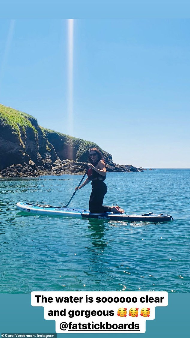 Keeping afloat: Carol has been enjoying paddle boarding in Wales during the heatwave