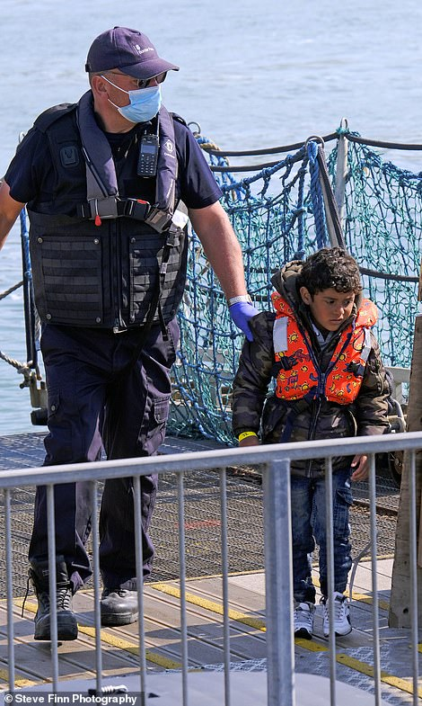 Child migrants wearing children's lifejackets are seen coming ashore at Dover Marina in Kent by Border Force officials