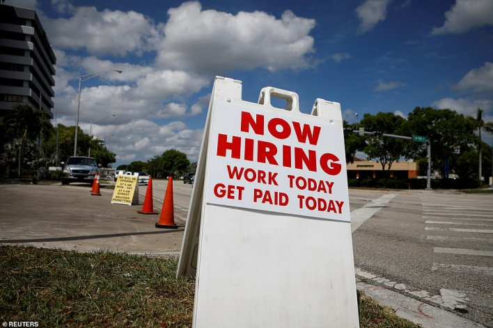 A 'Now Hiring' sign advertising jobs at a hand car wash is seen along a street in Miami, Florida in 202