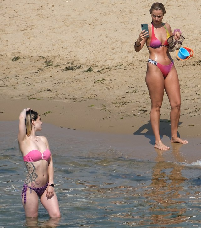 One woman takes a picture of another at Bournemouth beach in Dorset today as people enjoy the heatwave