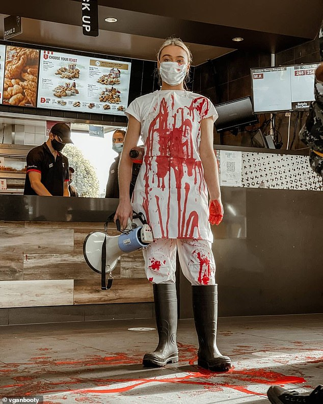 Tash Peterson is pictured during a disruptive protest at a Melbourne KFC soaking the floor in fake blood and berating customers