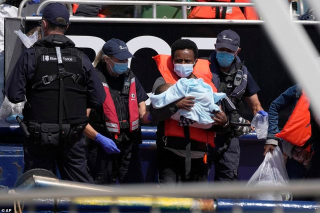 A man thought to be a migrant who made the crossing from France carries a child as they disembark from a Border Force vessel in Dover