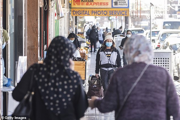 Pictured: People shopping in Lakemba, in Sydney's south-west. The region could be subject to harsher restrictions