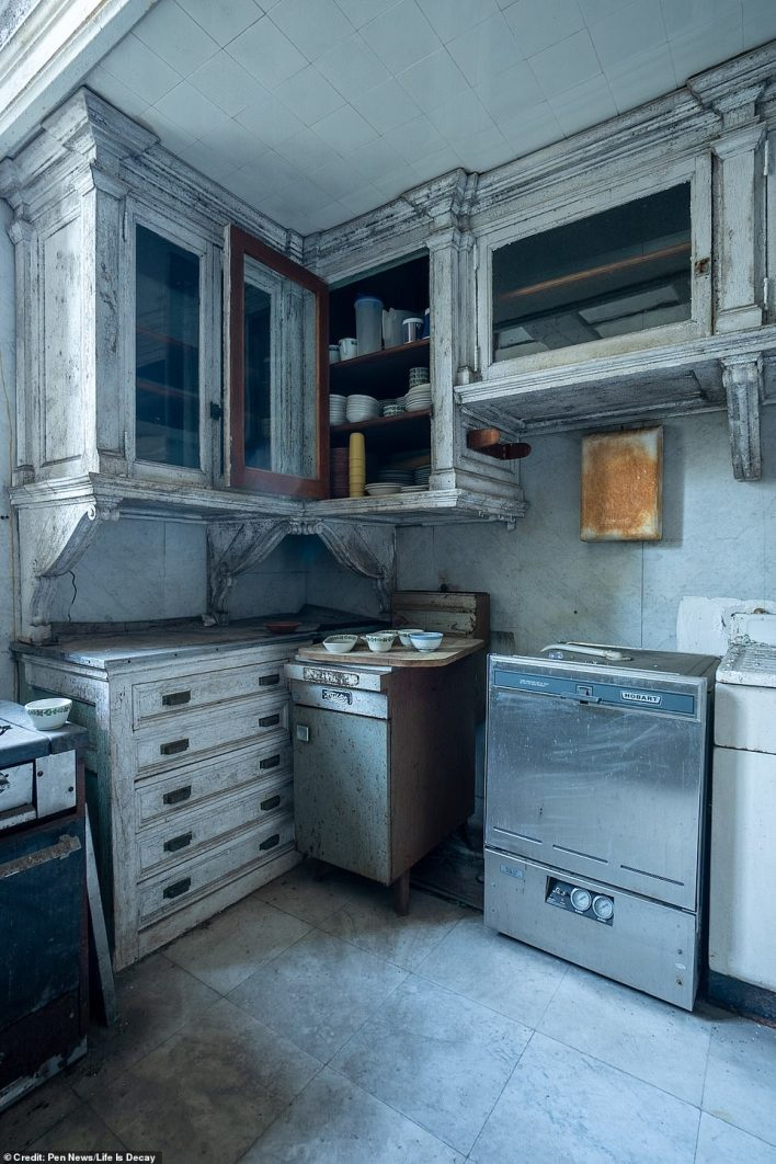 The kitchen cupboards are still filled with bowls and other items, but the units themselves are rickety and grimy