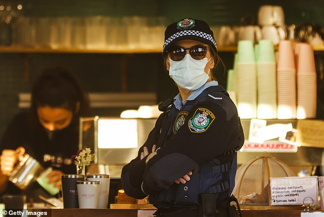 A police officer stands in a cafe at Bronte Beach on July 22. The eastern suburbs was at the centre of the city's outbreak, but most new infections are being recorded west of the city