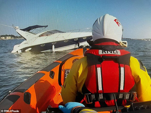 This is the dramatic moment a £150,000 yacht sinks in the sea off Sandbanks, sparking lifeboat crews into action to rescue a couple after the vessel became swamped by water