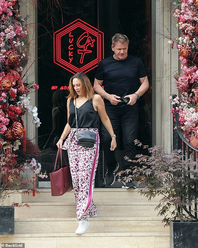 Looking good:Gordon Ramsay gave a glimpse of his toned arms in a black T-shirt as he left his Lucky Cat restaurant in London's Mayfair with a female friend on Thursday