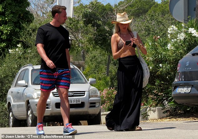 Floaty:The TV personality teamed the string piece with a floaty black skirt and wore her bright blonde hair loose, keeping the sunshine at bay beneath a woven cowboy hat
