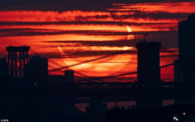 Pictured: the partial solar eclipse rises into an orange-tinged sky behind the Brooklyn Bridge and the east river in Manhattan, as seen from Bayonne, New Jersey on June 10, 2021