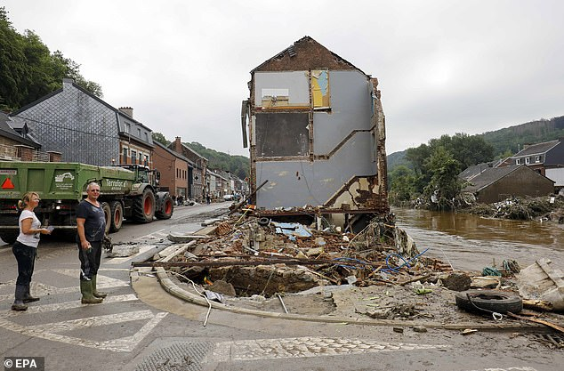 Residents survey the damage caused by days of heavy rainfall and flooding in Pepinster, Belgium, on Saturday