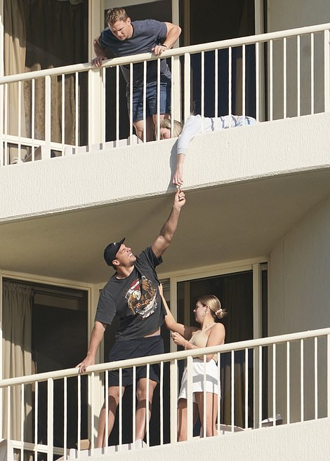 The pair are precariously hanging over the edge of their balconies as they pass the sweets across floors.There's no suggestion the other people pictured have broken the bubble's rules