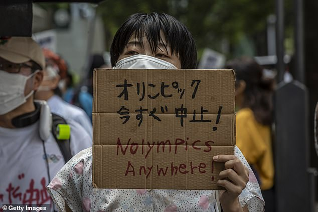 Protesters opposed to the Tokyo Olympics gather outside a torch relay venue in the Japanese capital to express their anger just hours before the Games officially begin