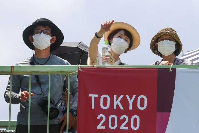 People excited about the arrival of the Games stand outside the National Stadium before the opening of the Tokyo Olympics