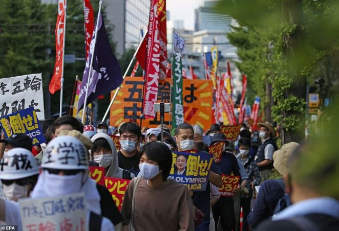 Protesters march outside the Tokyo Olympics' main stadium ahead of the Opening Ceremony