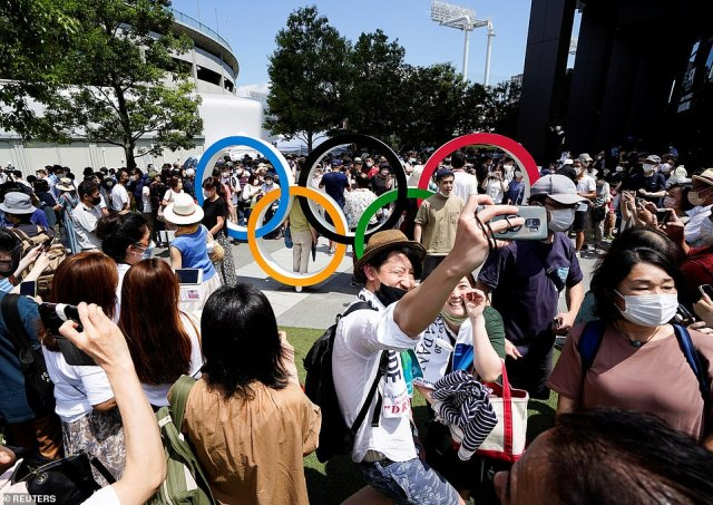 Sports fans gather outside Tokyo's main stadium to take pictures in front of the Olympic rings and soak in the atmosphere ahead of the Olympics opening ceremony