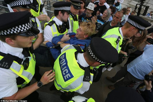 Police officers are pictured arresting and carrying away a demonstrator during the rally at Trafalgar Square in central London