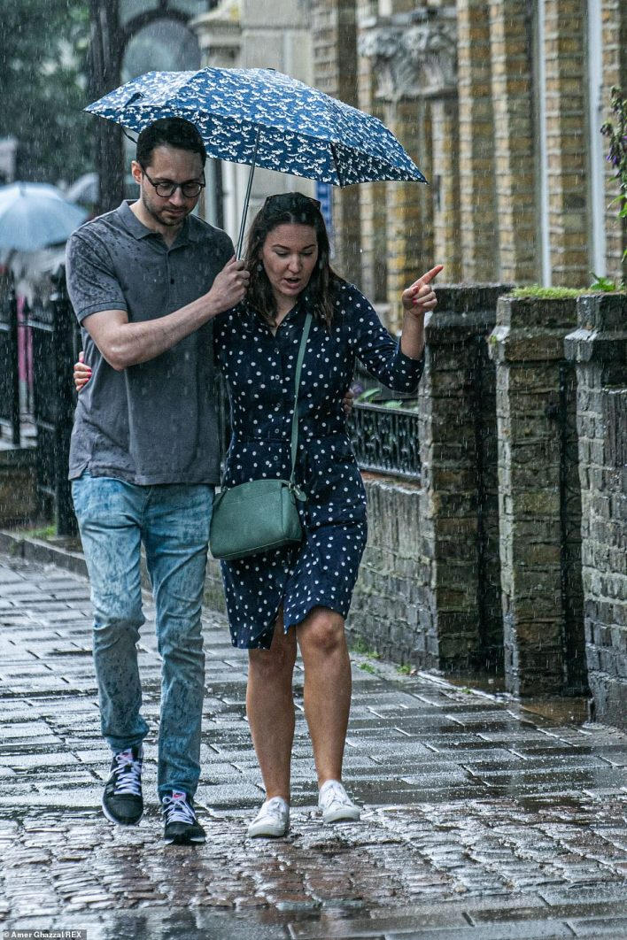 Two people cuddle up under an umbrella on a walk through Wimbledon Village during the heavy rain showers on Sunday afternoon