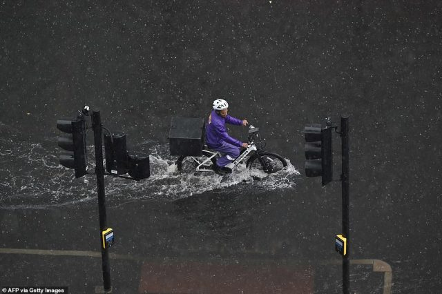 A cyclist wades through deep water on a flooded road in The Nine Elms district of London on Sunday