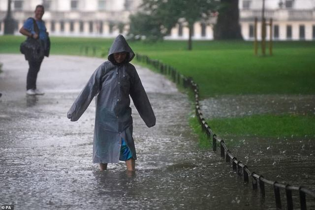 A woman walks through a flooded path in St James's Park in central London.Kingston Police, who oversee a borough in the amber zone for storms, warned motorists to 'drive carefully' and remember they are 'not driving a submarine'