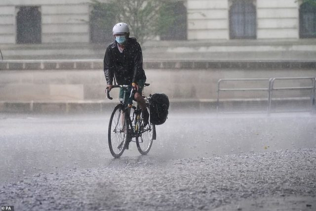 A cyclist rides through flood water in Horse Guards Road in central London as thunderstorms pelted the capital yesterday