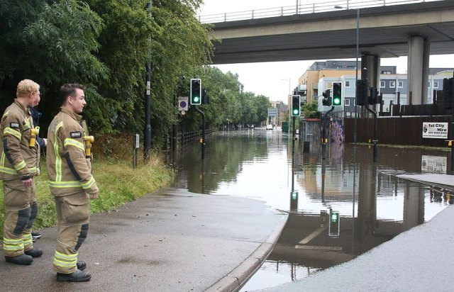 Pictured: London Firefighters look along Chigwell Road in south Woodford which goes under the A406. The Metropolitan Police have declared a 'major incident' in north-east London after heavy rainfall and thunderstorms caused flash flooding