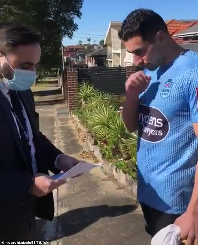 A group of investigators are seen waiting outside a Belmore home in Sydney's south-west on Sunday July 25 to issue the Sydney comedian with a penalty infringement notice