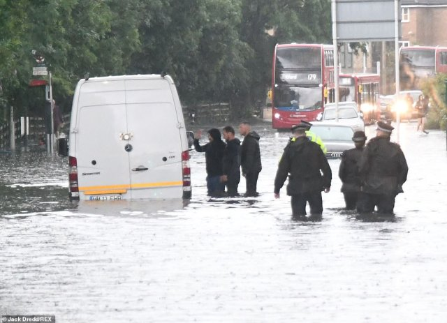 Police wade through deep flood water to assist a van driver whose vehicle is submerged in Chigwell Road, London, today