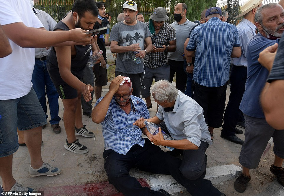 A injured man is helped by fellow protesters after he was hit on the head by a stone thrown at him during a demonstration outside the parliament building on Monday