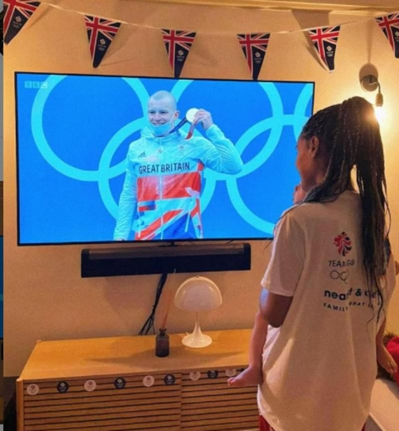 Adam Peaty's girlfriend Eiri and son George watch with pride as he collected his gold medal this morning in Japan