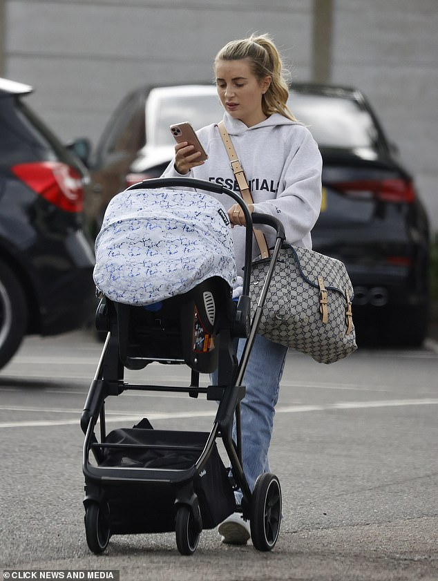 Designer: A large designer bag was strapped to Dani's chest, no doubt full of her little boy's essentials