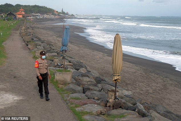 A lone police officer patrols a beach in Badung, Bali, on July 17 (pictured) with tourists locked out of the island since March 2020