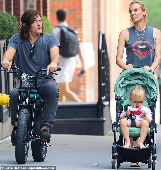 Here we go: she was in stroller duty on her last outing as her man climbed the sidewalk alongside them on his bike