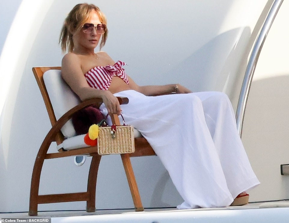 Earning Her Stripes: JLo looked flawless as she showed off her toned belly in a bikini top while relaxing on her mega-yacht