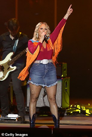 Fringe power: Her on-stage outfit was full of country cool accents including heeled cowboy boots and a fringed cowgirl shirt