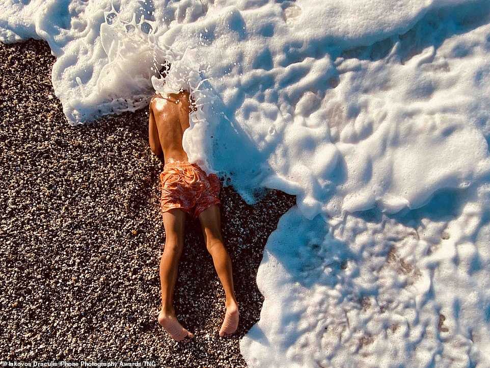 Pictured: A boy is photographed just as the waves crash over him on a beach in Greece. Iakovos Draculis's picture came second in the competition's category of Children