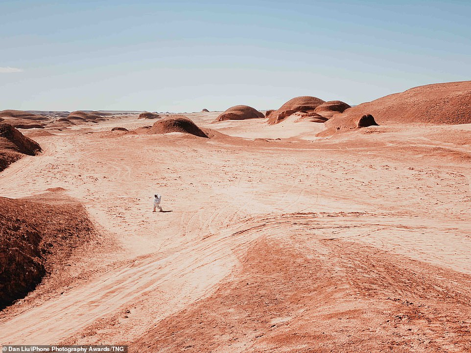A Walk on Mars: Second place went to this other-worldly picture of a man in a space suit walking across Mars-like terrain in Max Qinghai, China. Mounds covered in red sand are seen as far as the eye can see against a perfectly clear sky
