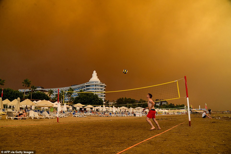 Beachgoers play on the sand as dark smoke descends over the coastal resort on Thursday amid mass forest fires in southern Turkey