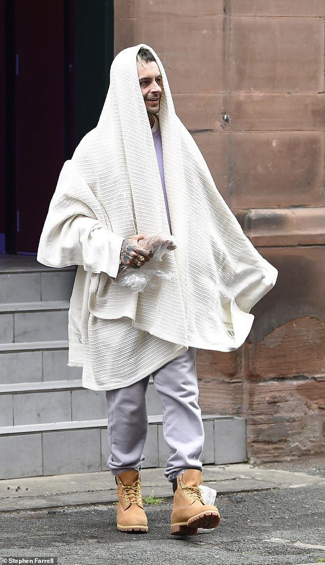 Laid-back:Joe cut a casual figure for the location shoot, donning grey tracksuit bottoms and a lilac jumper and draping a white blanket over his head at one point