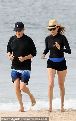His and hers: Paul headed out in blue colour block swim shorts and a black crew neck sweatshirt