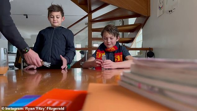 Pranked:Fitzy told his followers that he's decided to prank his sons, Hewy and Lenny, over their obsession with AFL trading cards by inserting a rare set in resealed card packs