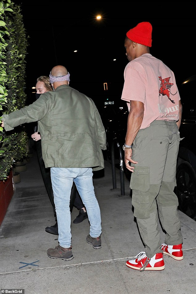 Evening out:Russell followed Adele into the eatery, with the singer donning a black face mask for the outing