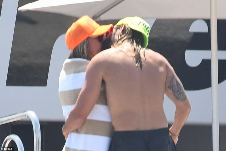 Packing on the PDA:The German-American model, 48, shared a kiss with her musician husband while wrapped in a towel