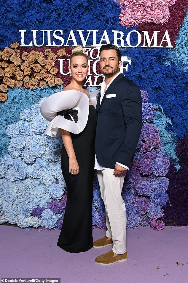 Stunning: Katy (left) looked elegant in black gown as she cosied up to her fiancé Orlando (right) at the star-studded gala
