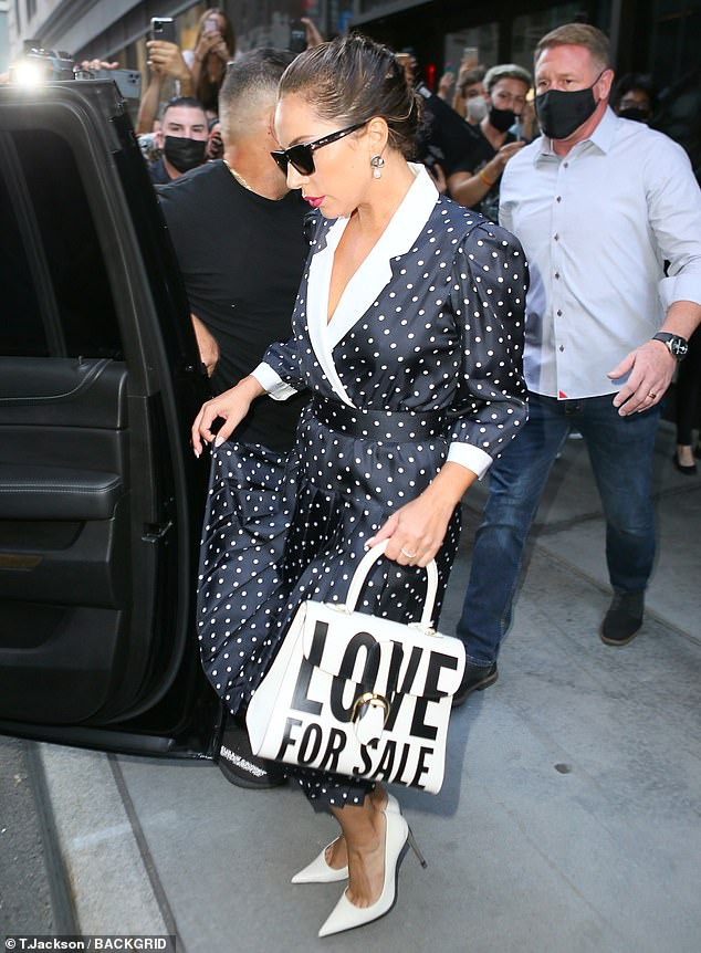 Self-promotion: She accessorized with a thick white handbag reading 'LOVE FOR SALE,' which is believed to be the name of her upcoming duets album with Tony Bennett