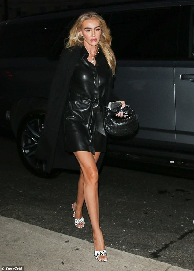 Stunning: The heiress, 32, flaunted her tanned legs in the racy leather shirt dress, which hinted at her cleavage as she strolled with her partner