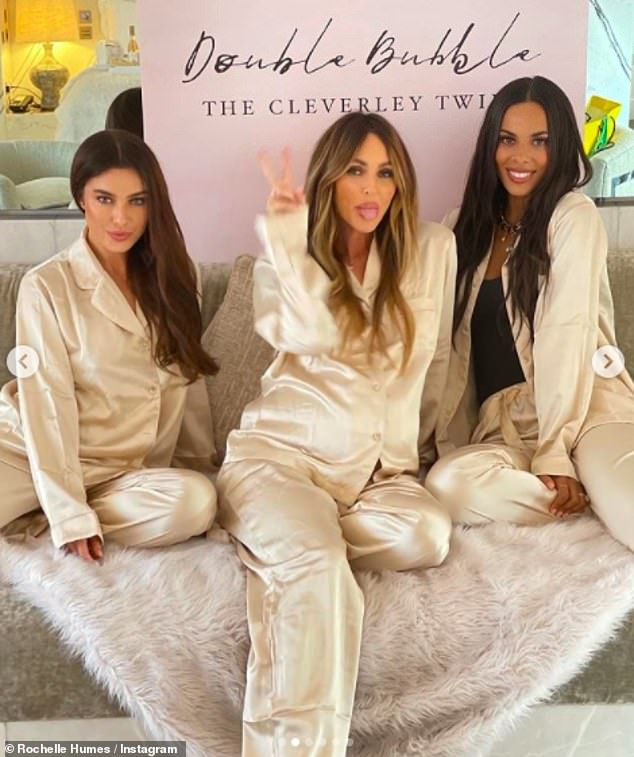 Sweet: In another photo, Rochelle, Georgina and a friend donned their silk comfies as they posed in front of a sign which said: 'Double Bubble. The Cleverly Twins'