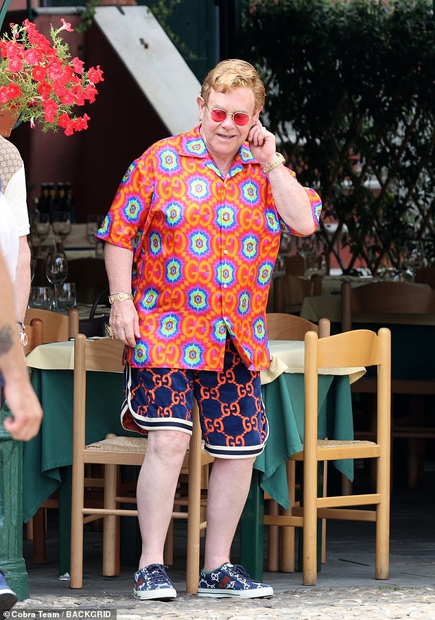 Exploring the village: Elton upped his height with a pair of navy and white sneakers, also from Gucci