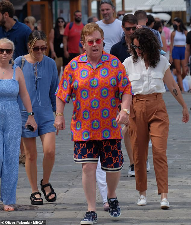 Must-have: Rocketman's hitmaker grabbed attention in a hallucinogenic-style orange Gucci shirt, adorned with blue floral prints